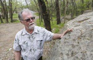 Археолог Жональд Блейксли указывает на сделанные человеком выемки в огромном валуне, который находится там, где когда-то находился 20-тысячный город Эцаноа. Фото: Travis Heying The Wichita Eagle