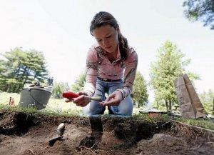 25-летняя волонтер Хизер Энгвер изучает предмет, найденный во время раскопок. 11.07.2014. Фото - Mike Groll / AP Photo
