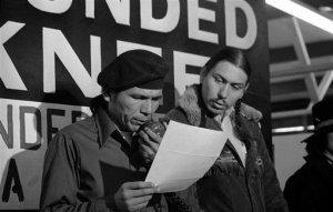 18 марта 1973 года. Лидер AIM Деннис Бэнкс (слева) зачитывает предложение правительства США. Рядом с ним стоит Картер Кэмп. Фото - Jim Mone / AP