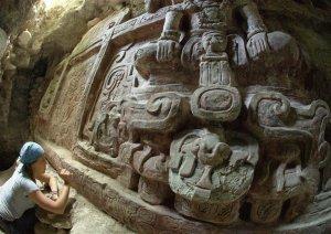 Археолог Аня Шетлер очищает надпись под древним фризом из штука, который был недаво раскопан в городище майя Хольмуль (Гватемала). Солнечный свет из входа в прорытый туннель освещает ноги правителя, сидящего на голове майяского духа горы. Фото - Франсиско Эстрада-Белли.