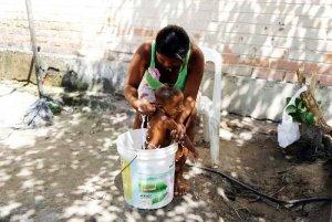 Индианка варао из Венесуэлы моет ребёнка в лагере для беженцев в Пакарайме (Бразилия)